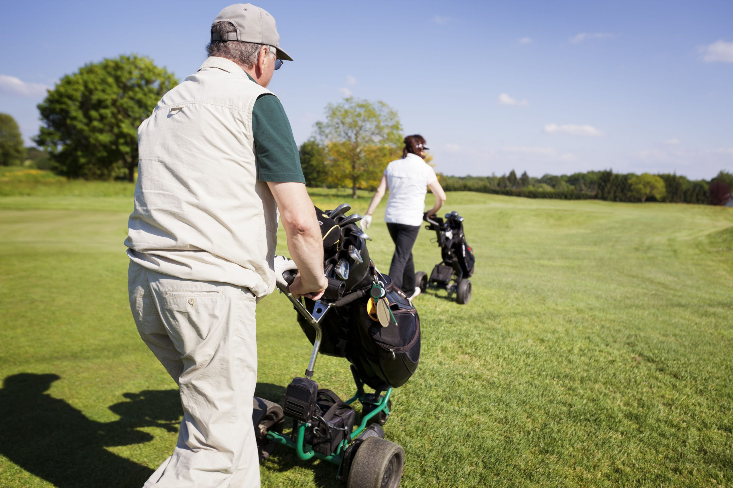 Couple walking on a gold fairway with golf trolleys